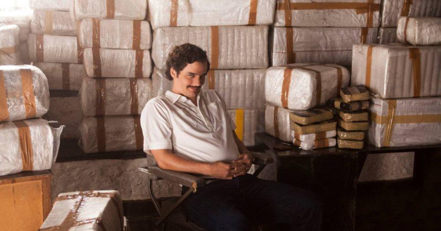 Pablo Escobar, protagonista de la serie Narcos, sentado junto a grandes cantidades de cocaína