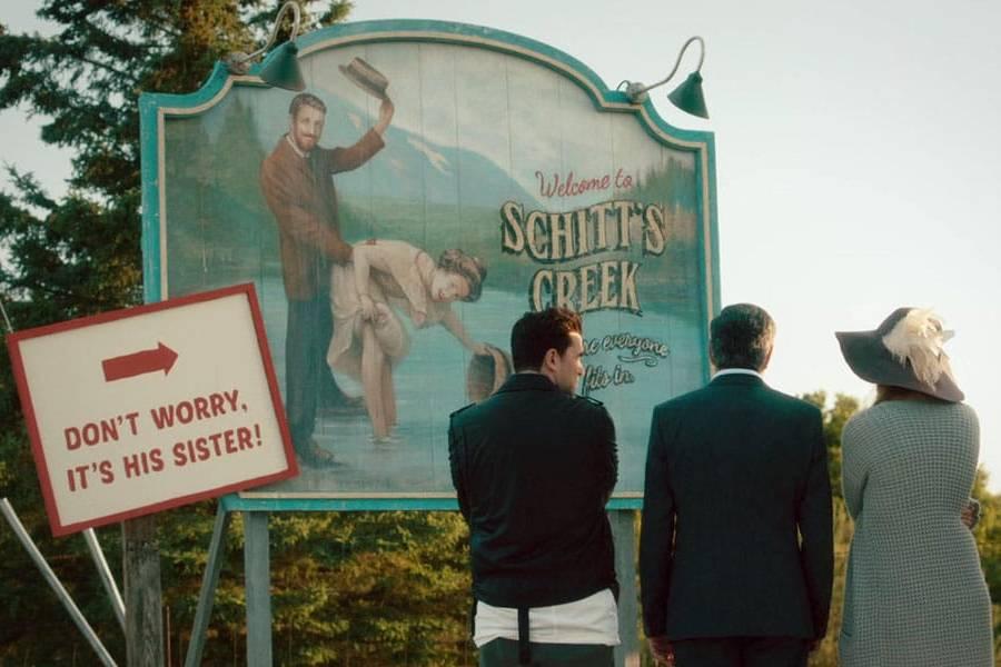 Familia Rose viendo el cartel de Schitt's Creek