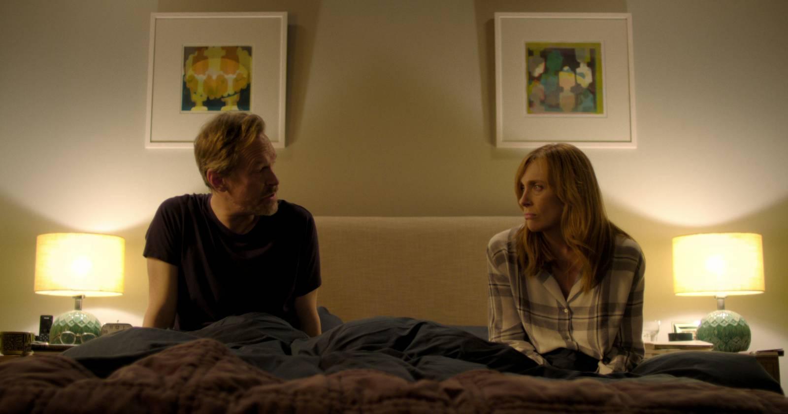 A la izquierda Steven Mackintosh como Alan, a la derecha Toni Collette como Joy. Ambos sentados en la cama conversando. En Wanderlust, serie original de Netflix.