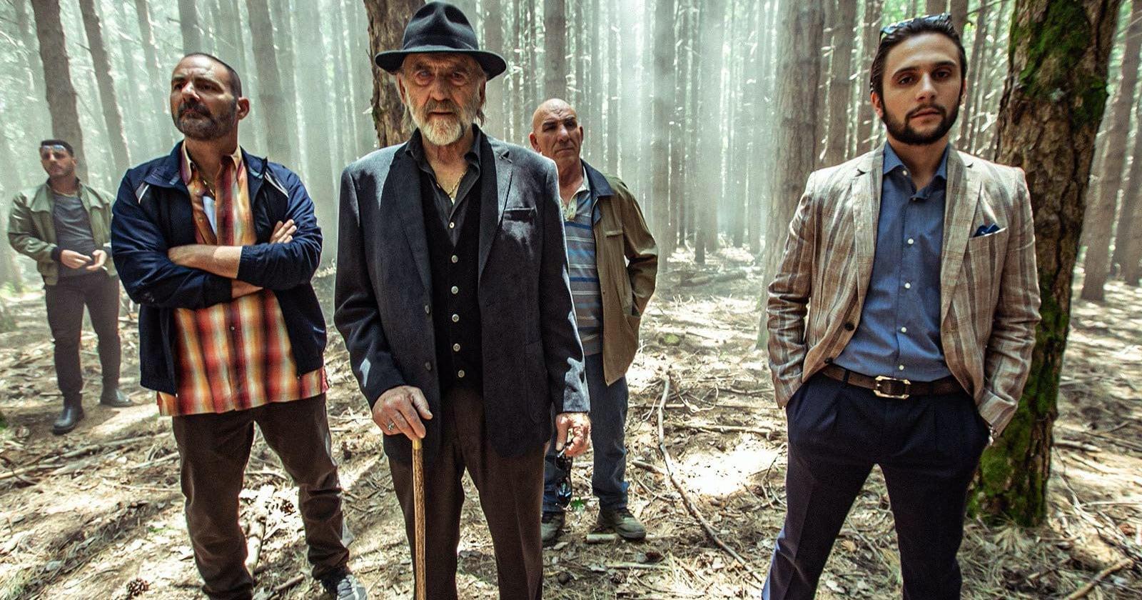 Cinco hombres, aparentemente mafiosos, miran de frente a la cámara en medio de un bosque neblinoso. Escena de Zerozerozero, serie original de Amazon Prime Video.