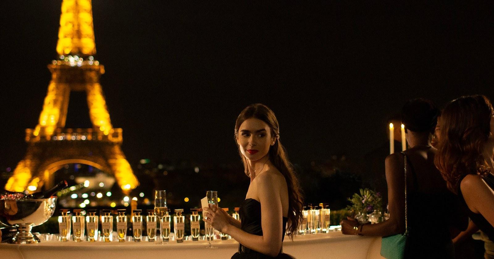 Lily Collins como Emily en París en una fiesta de gala nocturna con una copa de espumante en su mano y la Torre Eiffel con sus luces encendidas de fondo