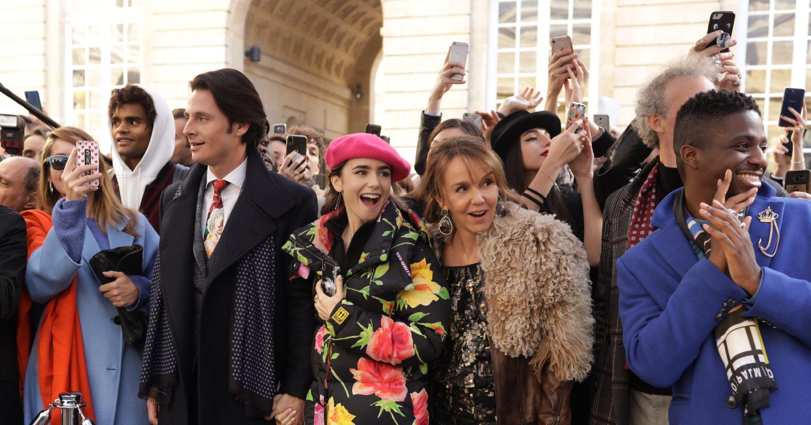 Emily en París en un desfile de modas en el exterior, en medio de una multitud tomando fotos con celulares, acompañada de sus colegas.