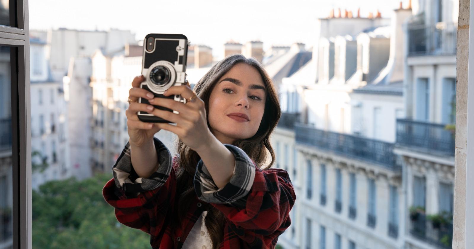 Emily en París en el balcón de su habitación Chambre de Bonne, tomándose una Selfie con los edificios blancos parisinos de fondo