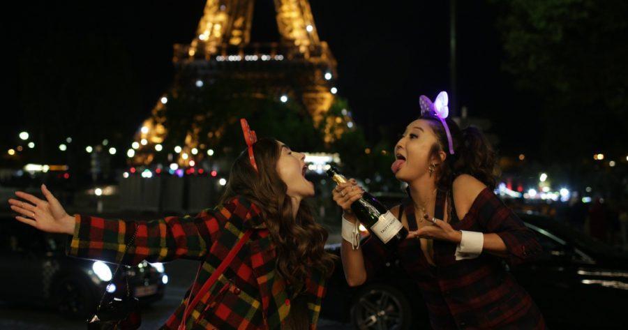 Emily en París con su amiga Mindy bebiendo espumante frente a la Torre Eiffel de noche