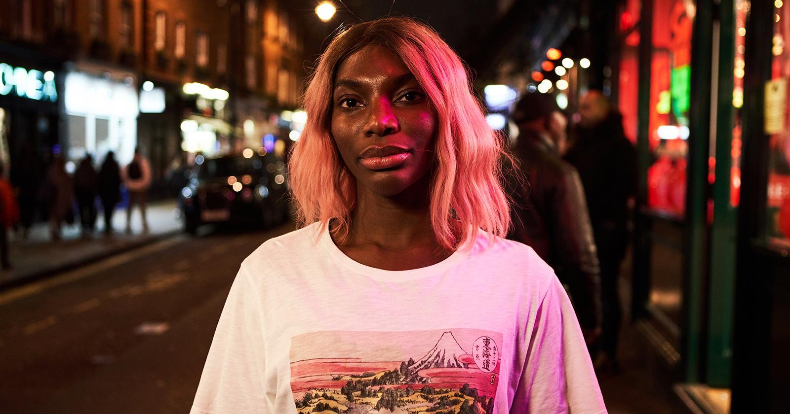 Michaela Coel, protagonista y creadora de I May Destroy You, mirando a la cámara de frente. Detrás, la ciudad de Londres iluminada por luces de neón.
