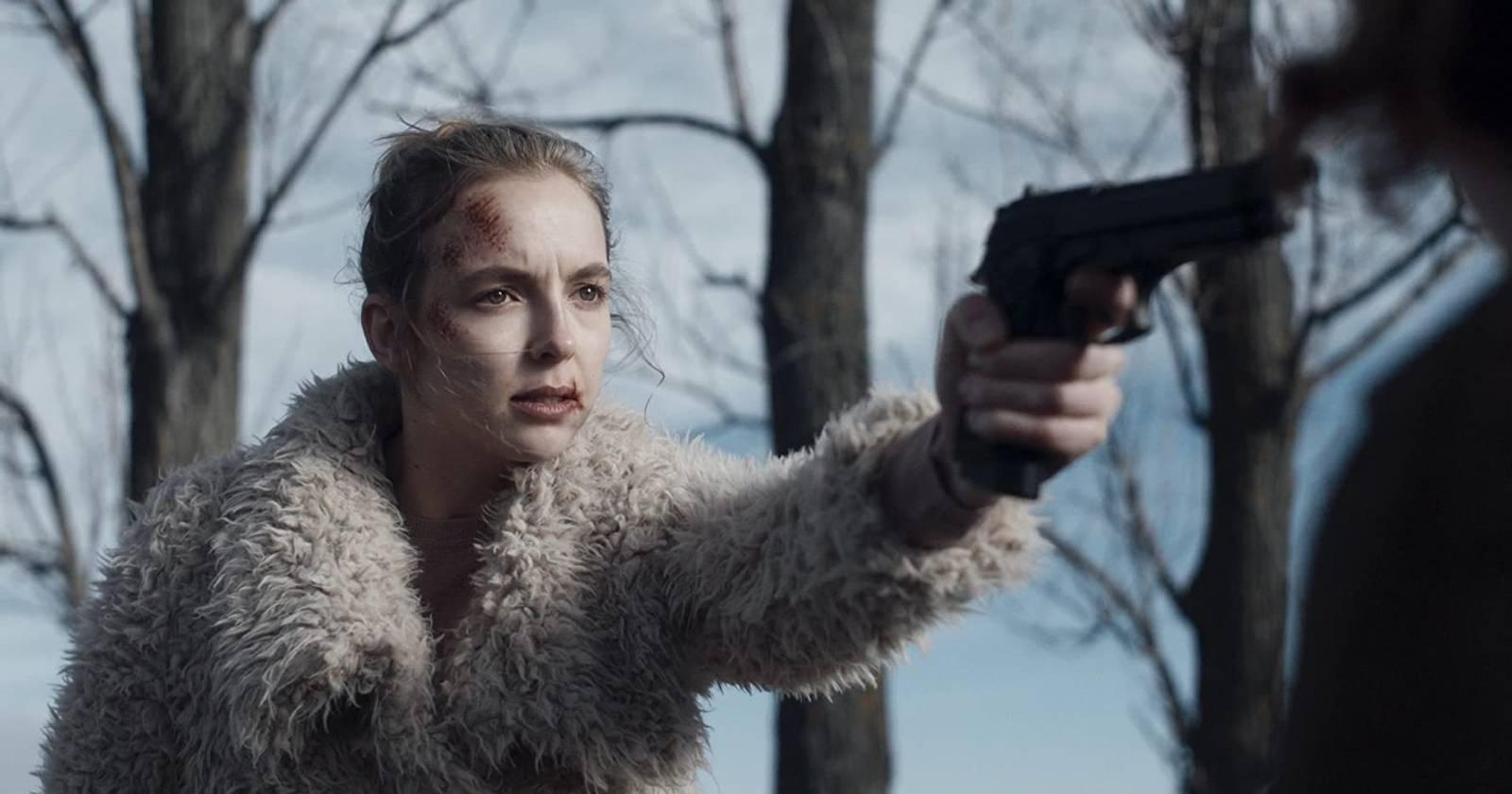 Killing Eve, Villanelle a la izquierda con la cara herida apuntando hacia la derecha una pistola frente a su rehén