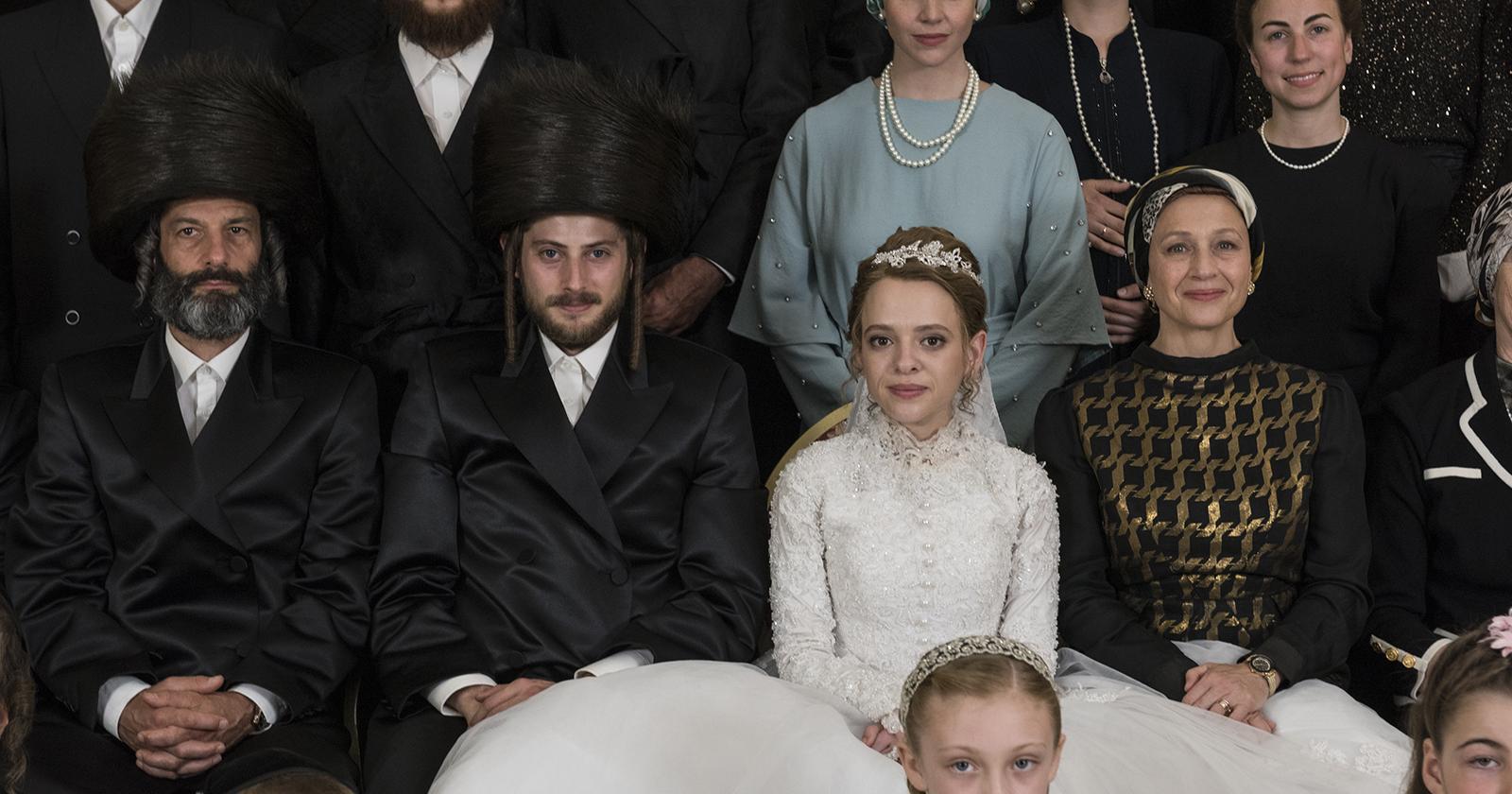 En la imagen vemos a Etsy, protagonista de la mini serie Poco Ortodoxa, en el día de su boda. Ella está sentada al medio de los miembros de su comunidad extremadamente religiosa. Esta fue una de las series 2020 más vistas de Netflix.