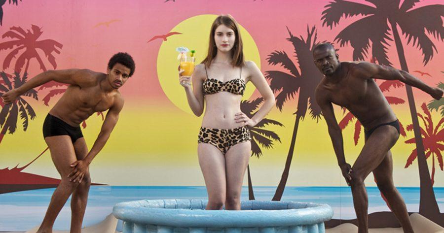 Alicia Rodríguez como Daniela Ramírez rodeada por dos modelos masculinos mientras sujeta un coctel dentro de una piscina de plástico con un fondo tropical y un bikini de animal print de la película Joven y Alocada