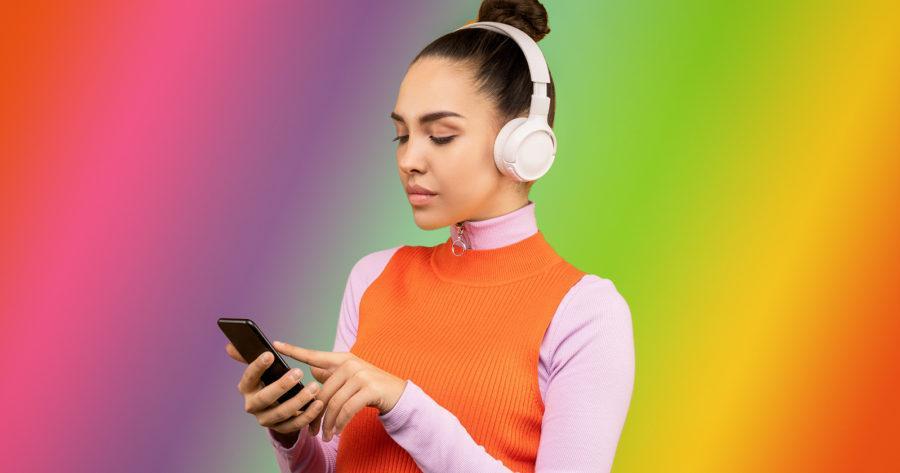 Mujer con audífonos y celular en la mano.