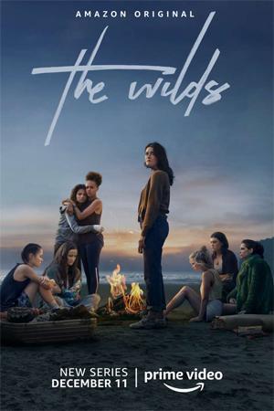 En esta imagen vemos tres protagonistas de Salvajes (The Wilds) sentadas en la arena, manchadas con tierra y despeinadas. De izquierda a derecha: Martha, Leah y Shelby. Esta serie la puedes ver en Amazon Prime