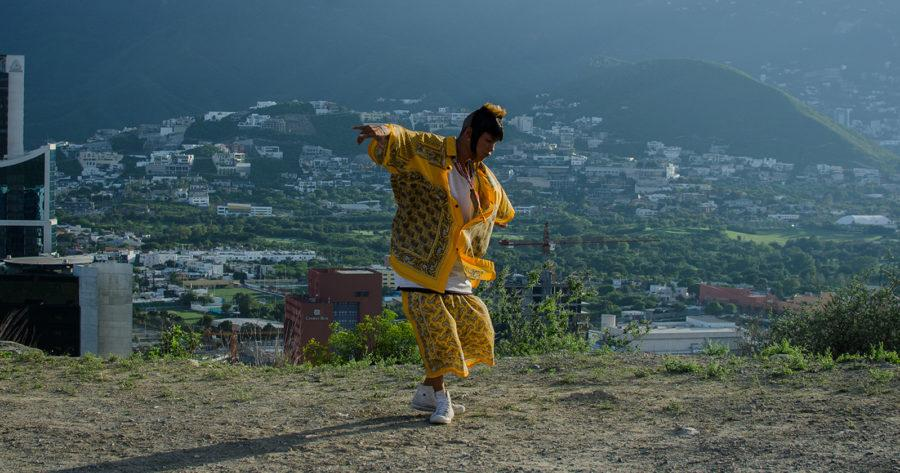 Juan Daniel García como Ulises en Ya no estoy aquí. Se le ve bailando cumbia en las alturas de una montaña, vestido de amarillo. A sus espaldas se ven a lo lejos los barrios de Monterrey.