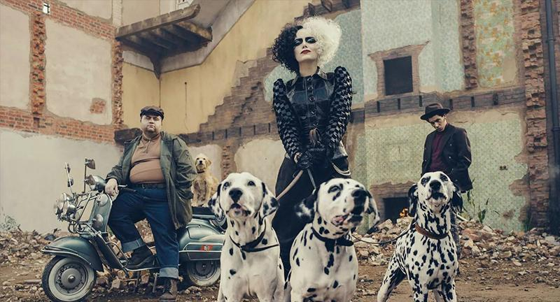 Emma Stone como Cruella de Vil, con tres dalmatas y dos hombres a las espaldas.