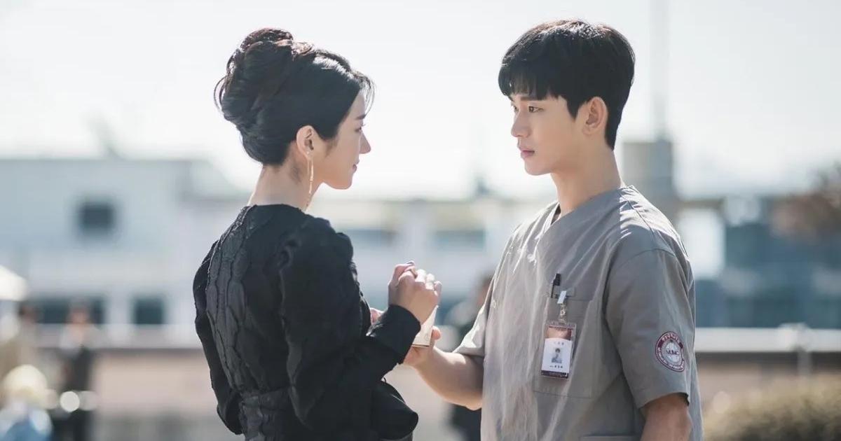 Protagonistas de la comedia romántica surcoreana Está bien no estar bien, tomados de la mano, mirándose de frente.