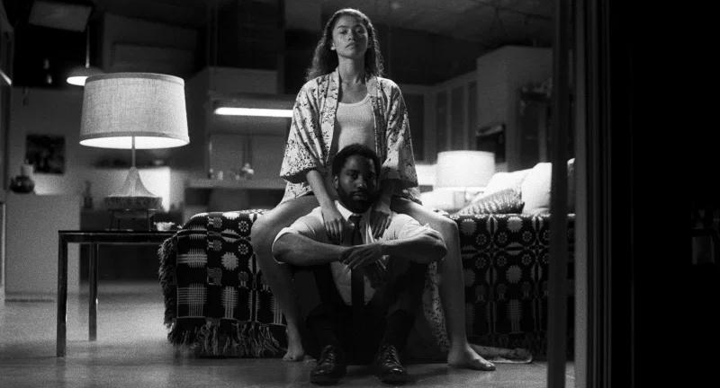 Fotografía en blanco y negro de Zendaya y John David Washington en una habitación matrimonial.