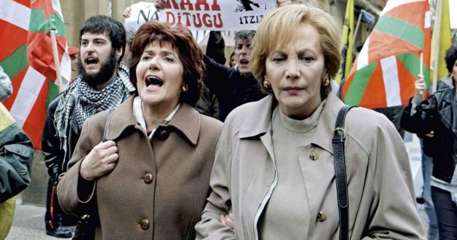Dos mujeres adultas en medio de una protesta. A sus espaldas, manifestantes con lienzos y banderas.