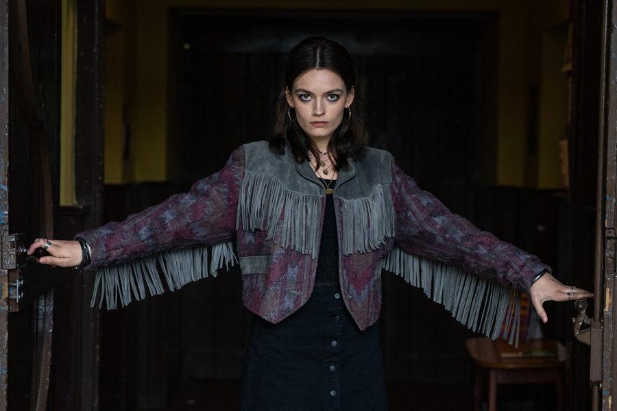 Emma Mackey como Maeve Wiley en la segunda temporada de Sex Education, se la ve con los brazos abiertos, con una actitud empoderada, vistiendo una chaqueta de cuero con flecos.
