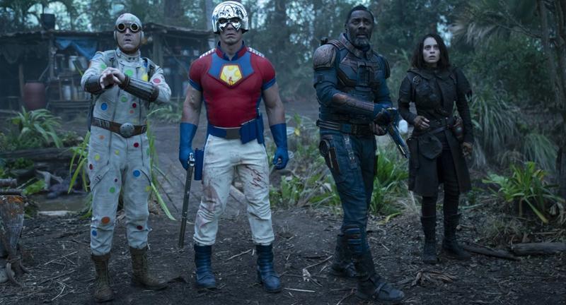 Grupo de cuatro miembros de Suicide Squad en un fondo de bosque devastado.