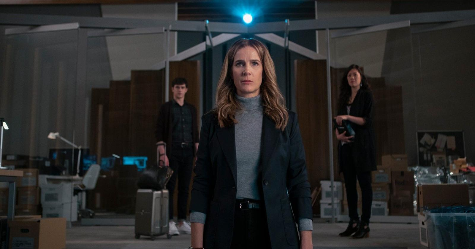 Rachel Griffiths como Gretchen Klein en Salvajes. En primer plano frente a la cámara y detrás de ella la luz de un proyector. A su lado, dos de sus empleados.