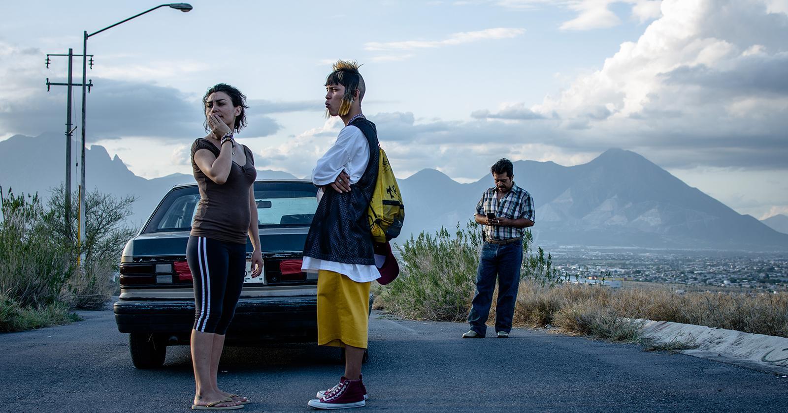 Escena de Ya no estoy aquí en que Ulises abandona Monterrey. Se le ve parado en una carretera, junto a un auto, despidiéndose de una mujer.