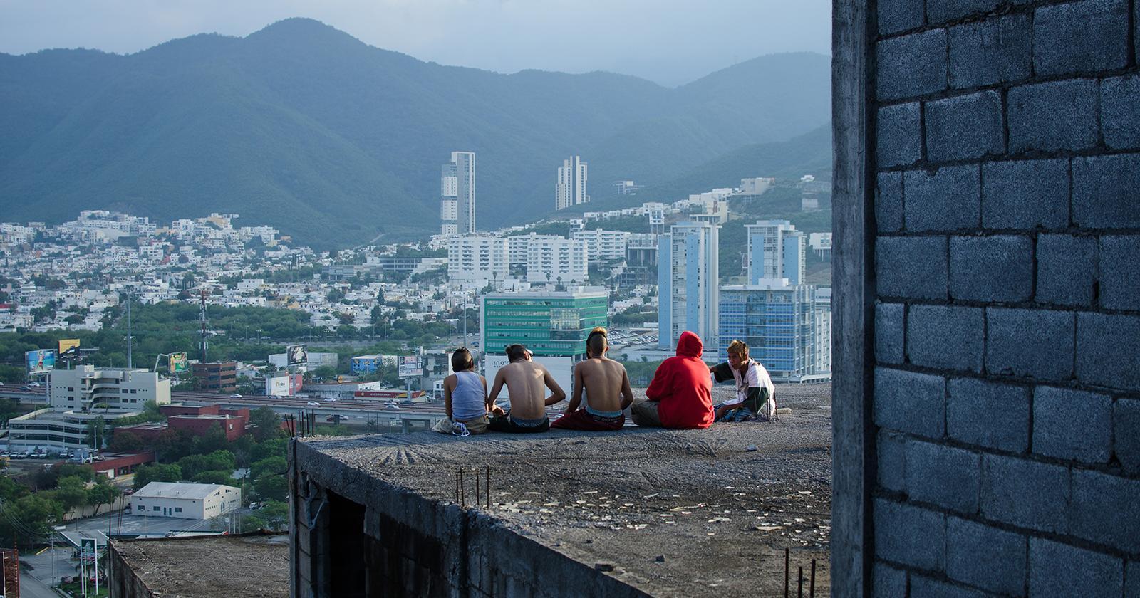 Ulises y sus amigos de espaldas, sentados en una construcción aparentemente abandonada, mirando desde las alturas los barrios de Monterrey.