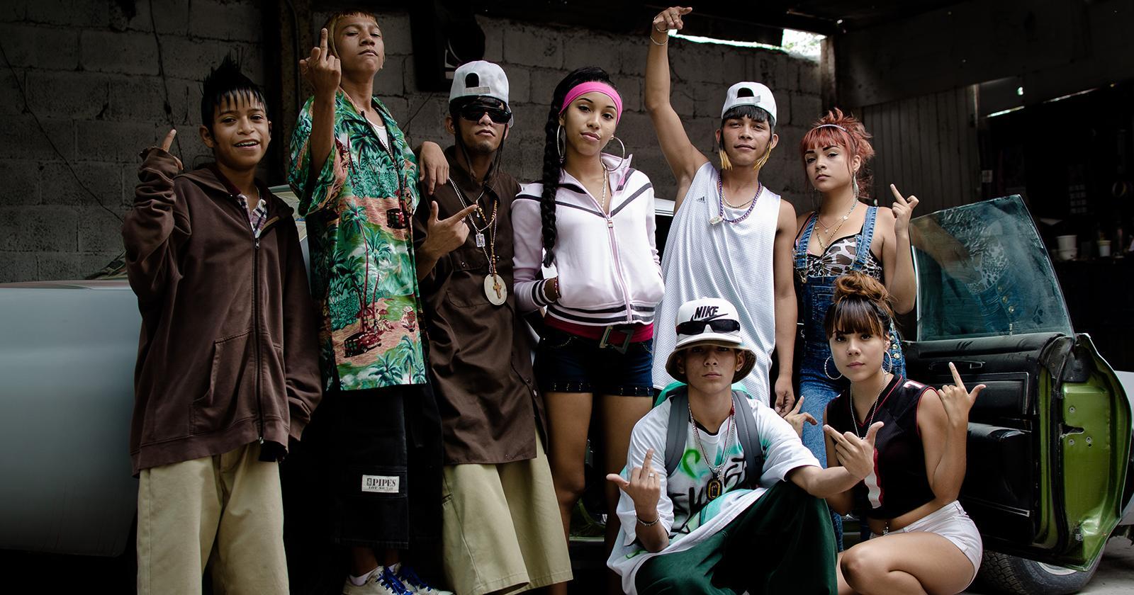 Grupo de ocho jóvenes caracterizados con la estética característica de los Kolombia. Peinados extravagantes y vestimentas coloridas y holgadas.