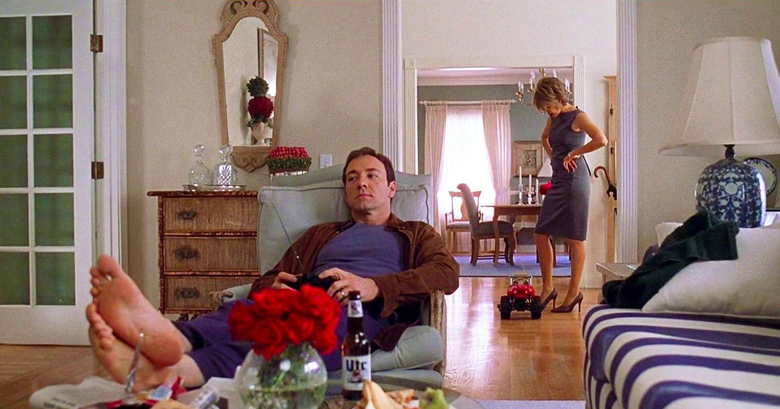 Lester (Kevin Spacey) tendido sobre un sillón. Detrás, Carolyn (Annette Bening) pasando la aspiradora. Escena de American Beauty.