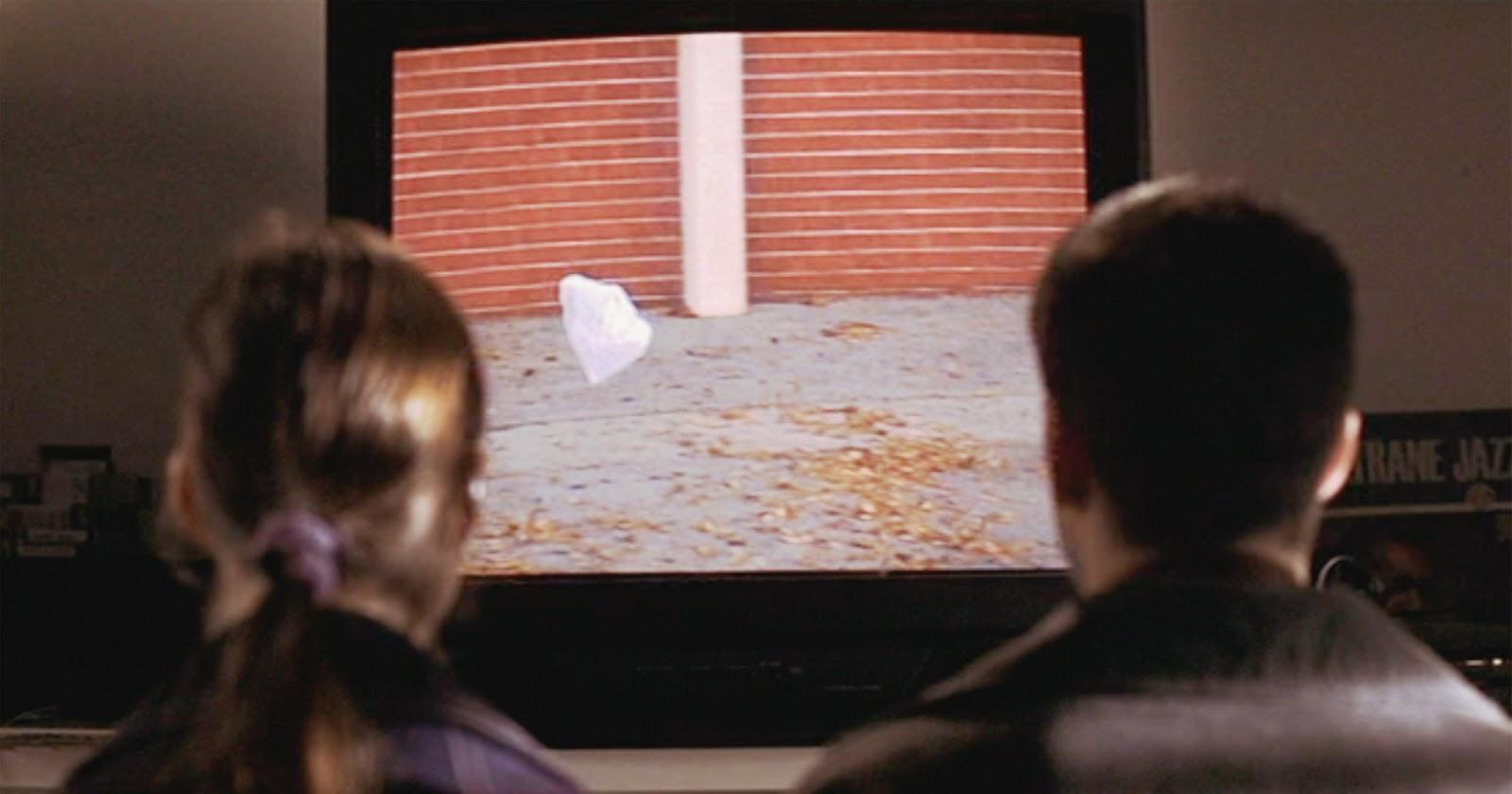 Jane (Thora Birch) y Ricky (Wes Bentley) de espaldas frente a un televisor, contemplando la famosa escena de la bolsa plástica bailando al viento.