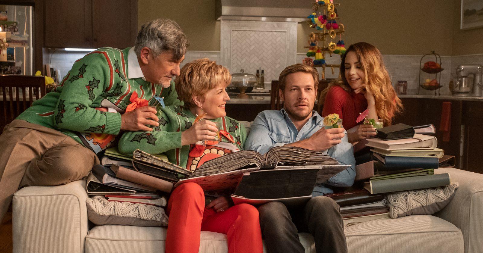 Luke Bracey como Jackson en Amor de calendario en la fiesta de navidad con la familia de su cita sentados en el sillón