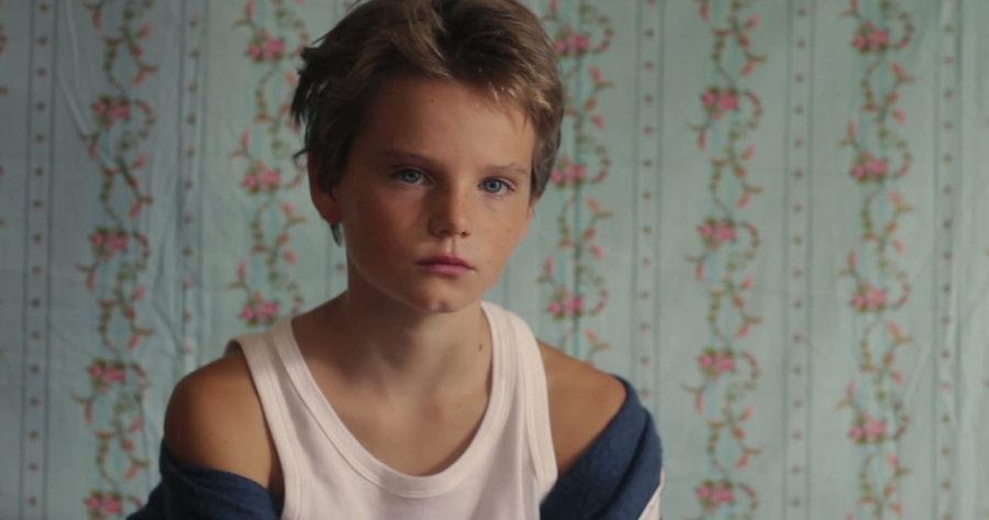 Zoé Héran, con el pelo corto, sobre un fondo de papel tapiz celeste con flores rosadas. Escena de Tomboy.
